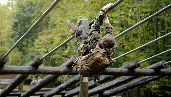 A female Marine goes through an obstacle course, one of the tasks of the combat endurance test.