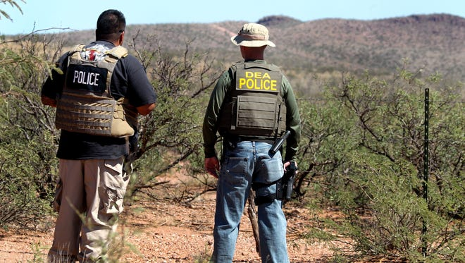 Det. Bill Silva, left, with the Bisbee Police Department, and an unnamed agent with the Drug Enforcement Administration patrol a fence line east of Naco, Ariz., after a Border Patrol agent was killed early Tuesday.