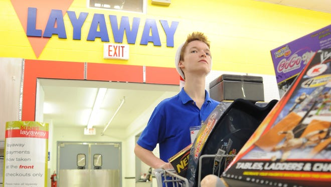 Colton Coots pushes a cart of toys out of the layaway department at Kmart in Jonesboro, Ark.