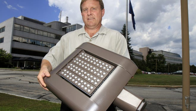 Fred Barnett, director of facilities at National Life Insurance Co., holds an LED light fixture that will replace older pole lights in Montpelier, Vt.  Such steps are boosting energy efficiency in many states.