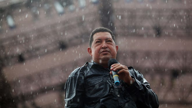 Under pouring rain, Venezuela's President Hugo Chavez holds a microphone during his closing campaign rally in Caracas, Venezuela, on Thursday.