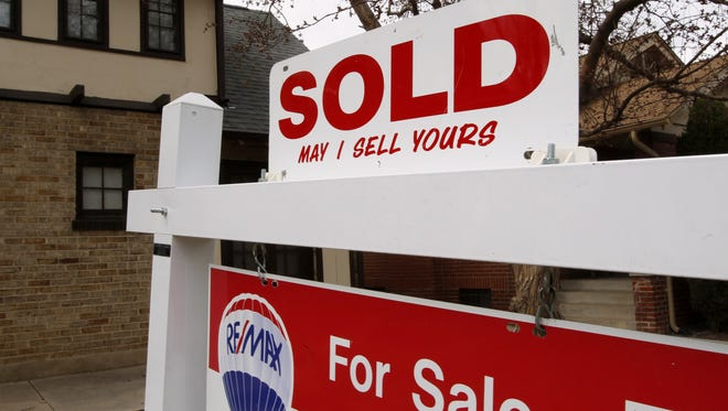 Sign stands outside home for sale in south Denver.