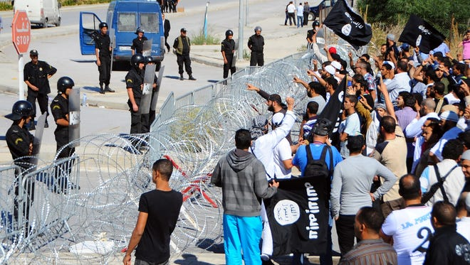 Protesters face-off against riot police officers guarding the U.S. embassy in Tunis on Sept. 14.