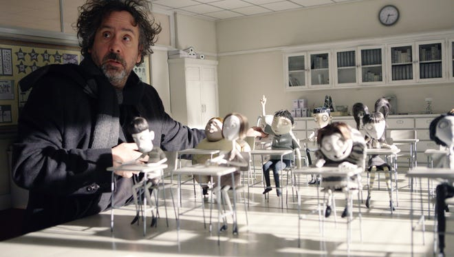 Director Tim Burton works with some of the stop- action figures for hiss animated motion picture 'Frankenweenie.'