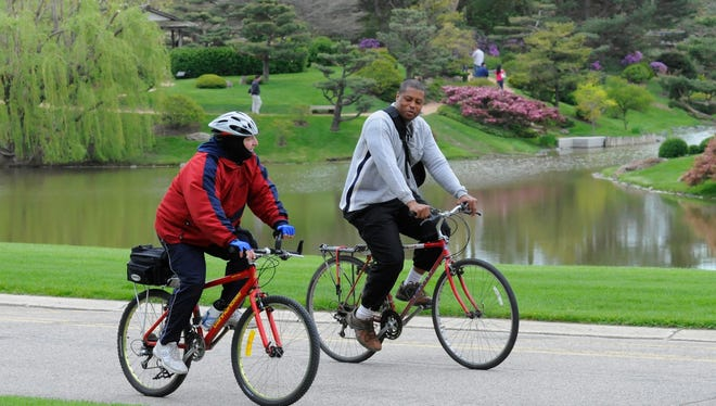 """Bicycling along the Chicago Botanic Garden's East Road is a pleasure in any season. On this chilly spring day, cyclists pass in front of the  lovely """"Garden of Three Islands."""""""