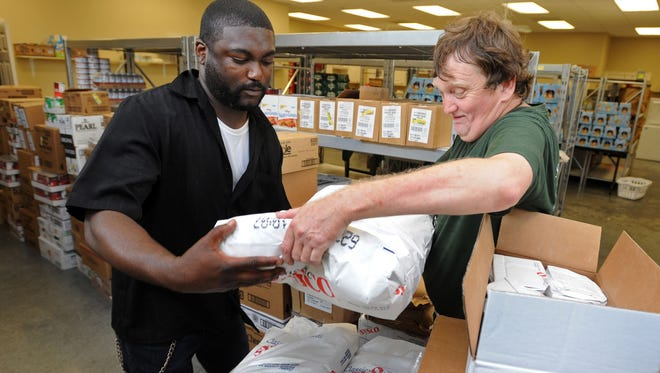 Jacques Smith, left, and Eddie Graves sort a shipment of food donated through the Extra Table at the Edwards Street Fellowship Center's food pantry in Hattiesburg, Miss.