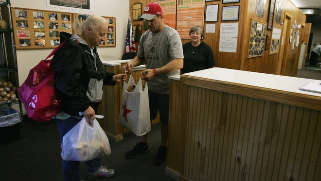 Judy Slover, 58, receives food from volunteer Mike Lacks of Freehold Township and Director Jeanne Yaecker at Freehold Area Open Door.
