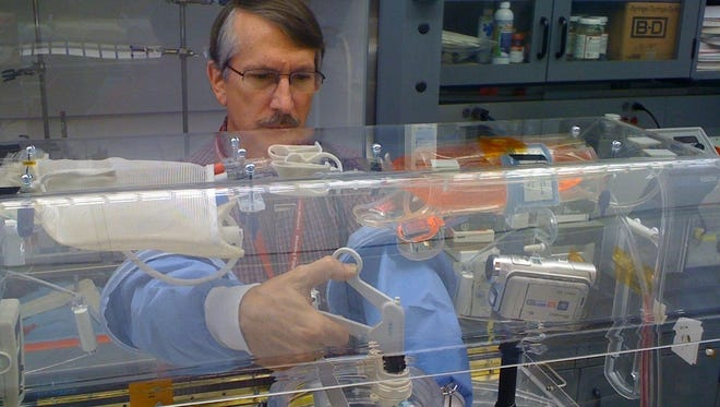 George Pantalos, a University of Louisville professor of surgery and bioengineering, tests a prototype of surgical device designed to aid surgery in zero-gravity during long space missions.