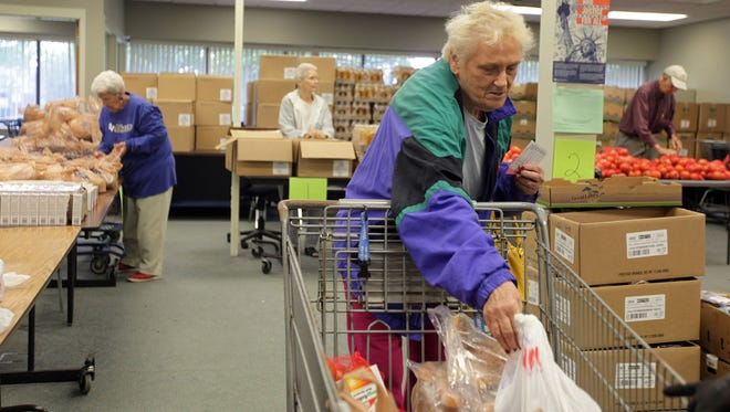 Food pantry client Lucy Corbitt collects food at Forgotten Harvest, a mobile food pantry in Livonia, Mich.