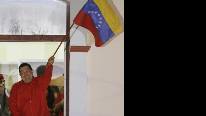Venezuela's President Hugo Chavez waves a Venezuelan flag as he greets supporters at the Miraflores presidential palace balcony in Caracas on Sunday.