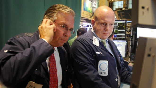 Michael O'Connor, right, of Getco Securities and a fellow trader work on the floor of the New York Stock Exchange.