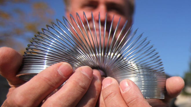 POOF-Slinky, Inc., President and CEO, Ray Dallevecchia Jr., holds one of the most iconic toys since the 1940's , a slinky, that his company distributes.