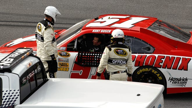Kurt Busch drove away from these safety workers without wearing his helmet during Sunday's race at Talladega. NASCAR parked him for the rest of the race.