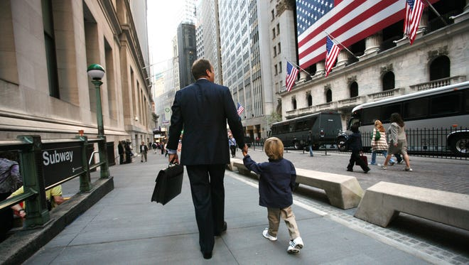 A businessman and his son walk past a flag-decked New York Stock Exchange in this file photo.