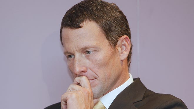 Lance Armstrong listening to a fellow cancer survivor during a news conference in 2011.
