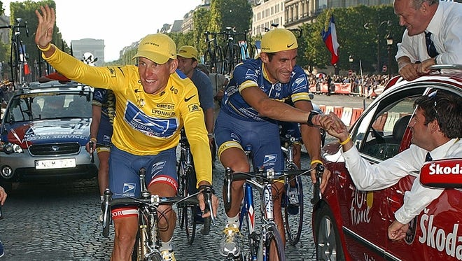 Lance Armstrong, left, celebrates his sixth Tour de France victory next to teammate George Hincapie, who now describes the doping they participated in.