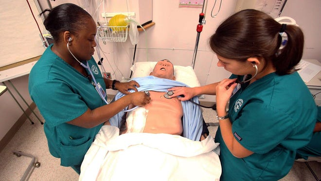 Nursing students Charlyndra Lucious, left, and Tiffany Pendley check vital signs on a dummy patient. Nursing is a high-demand area but may not be the right fit for you.