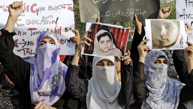 Pakistani members of Minhaj-ul-Quran Women League hold up pictures of 14-year-old schoolgirl Malala Yousufzai in Lahore, Pakistan, on Wednesday.