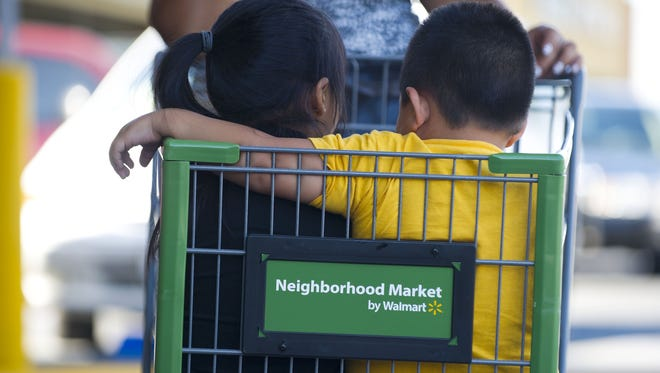 Danny Diaz rides in a shopping cart with his sister Brianna at the Walmart Neighborhood Market in Panorama City, Calif.