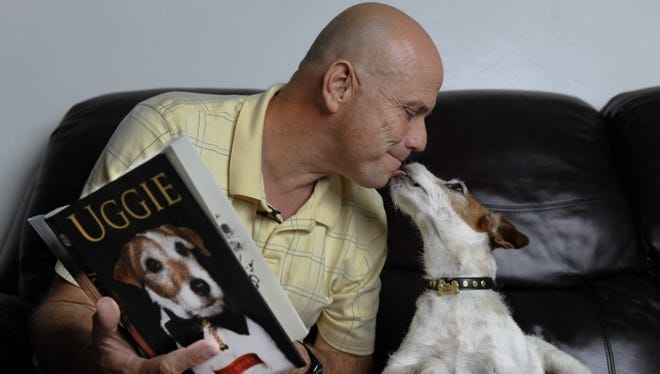 Uggie give trainer Omar von Muller a kiss as they read his new book.