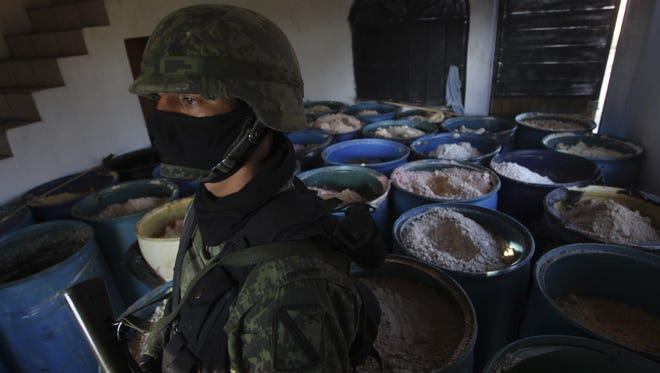 A soldier stands in a room full of barrels containing white and yellow powder after a seizure of 15 tons of pure methamphetamine at a small ranch in Tlajomulco de Zuniga, on the outskirts of Guadalajara, Mexico.