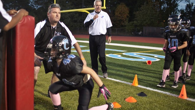Safety coach Tom Healy (white shirt) provides instruction to youth players during a tackling drill at Centreville High School in Clifton, Va.,