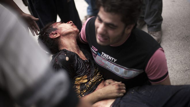 A Syrian man holds the body of his brother, killed by Syrian Army shelling, at a hospital in Aleppo, Syria.