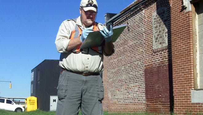 Alex Cox of the Maryland Department of the Environment makes notes about the location of a soil sample he collected on Sept. 11, 2012 from a neighborhood around the former location of Industrial Metal Melting in Baltimore. The factory, which was located at 108 E. Barney St., once melted lead. In 2006, EPA contractors visited the site and recommended soil testing because so many homes were nearby. But the EPA never did the testing and state regulators were unaware of the federal report until USA TODAY provided it to them.