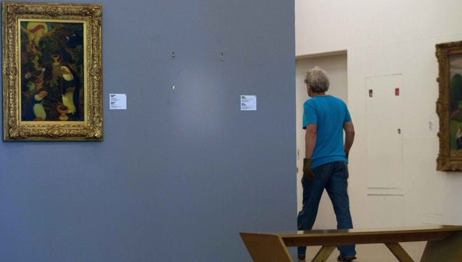 """The empty space where Henri Matisse' painting """"La Liseuse en Blanc et Jaune"""" was hanging, right, is seen next to a painting by Maurice Denis, left, at Kunsthal museum in Rotterdam."""