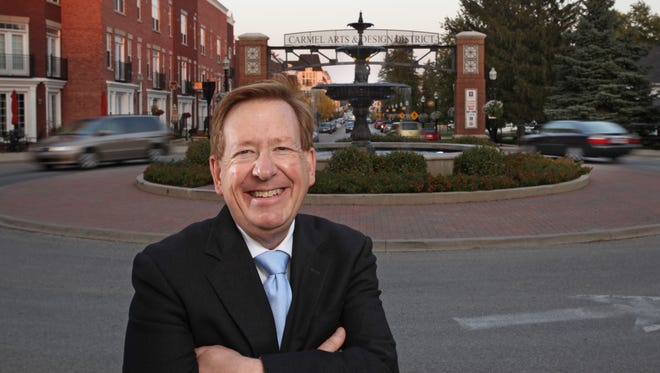 Carmel, Ind., Mayor Jim Brainard stands in front of one of the city's famous roundabouts at the entrance to the Arts and Design District.