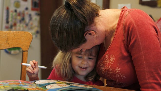 Evelyn Rose, 4, gets a hug as she enjoys craft time by coloring with her mother Meghann Rose in their Brighton, N.Y. home.