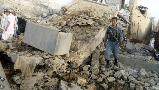 An Afghan police officer walks over debris after an explosion in Kandahar south of Kabul, Afghanistan, Aug. 28.