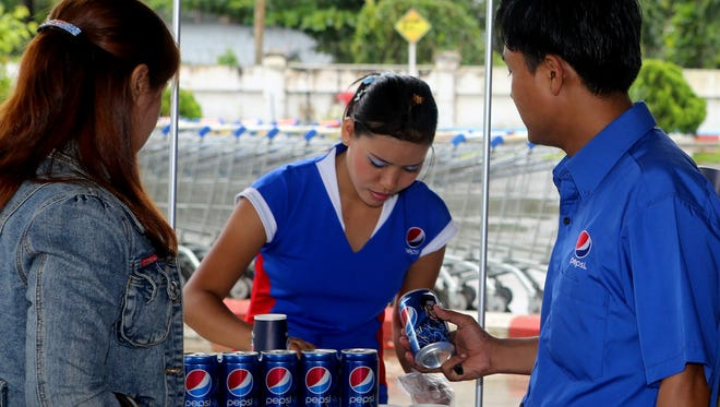 Pepsi hands out samples Aug. 9, 2012 at the Capital Hypermarket in Yangon, Myanmar.