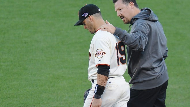 Giants second baseman Marco Scutaro, is attended to by a team trainer after colliding with Cardinals left fielder Matt Holliday on a double play attempt during Game 2 of the NLCS at AT&T Park on Monday.