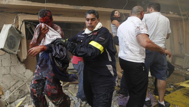 A Lebanese rescue worker, center, helps an injured man at the scene of an explosion  in the mostly Christian neighborhood of Achrafiyeh, Beirut, Lebanon.