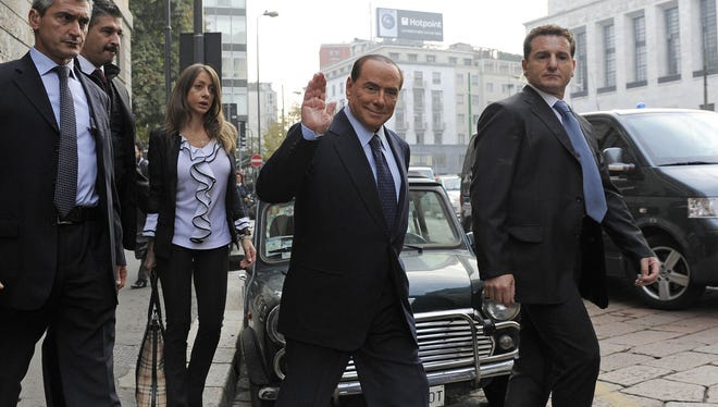 Former Italian Premier Silvio Berlusconi salutes as he arrives for a court hearing in Milan, Italy, on Oct. 19.