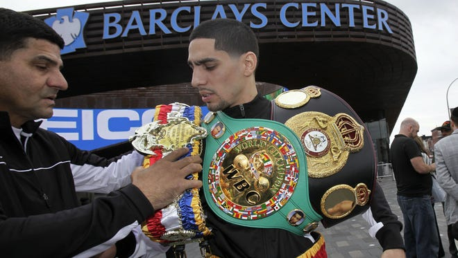 Boxer Danny Garcia, right, from Philadelphia, is assisted with his belts by his father, Angel this week in Brooklyn.