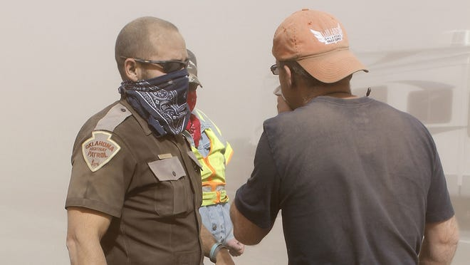 Oklahoma Highway Patrol trooper Jason Ross, left, wears a bandana to filter out heavy dust as he works at the scene of a multi-vehicle accident on Interstate 35.