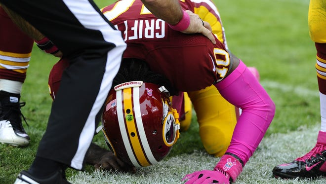 Redskins quarterback Robert Griffin III is assisted by an official after taking a hit against the Atlanta Falcons that caused a concussion. The team was fined $20,000 for not announcing the concussion quickly enough.