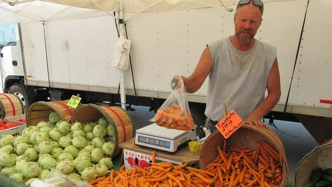 David Witte, a farmer in West Bend, Wis., packages carrots for sale at a farmers market in West Allis, Wis.