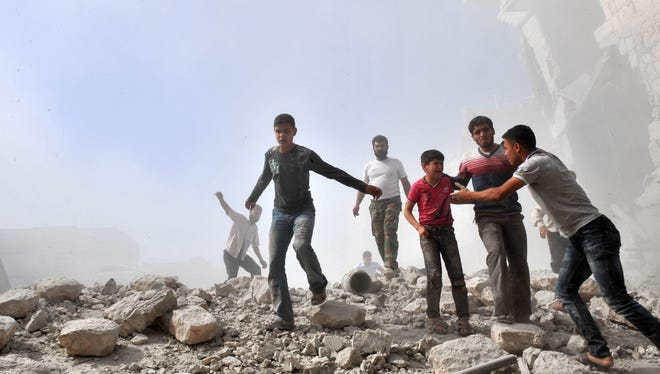 Syria youths react following an airstrike by Syrian government forces in Maaret al-Numaan on October 18, 2012.