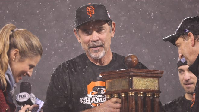 Giants manager Bruce Bochy, holding the NL Championship Series trophy Monday, has pushed all the right buttons in the postseason.