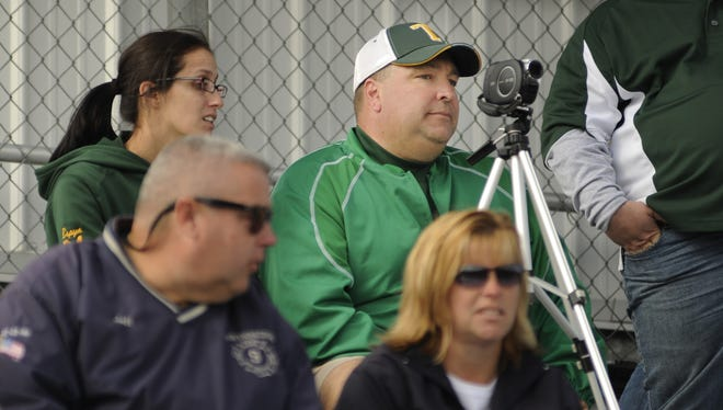 Suspended Tantansqua Pop Warner football coach Erik Iller operates a video camera from the stands during a game.
