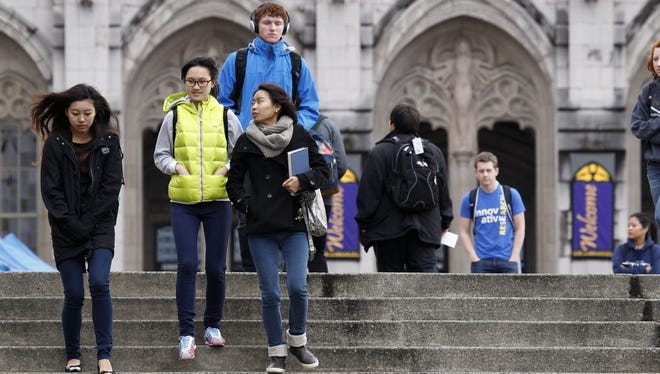 University of Washington students walk on the campus between classes in Seattle. It is the state's most selective public university.