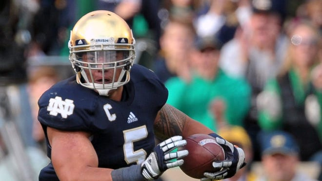 Notre Dame linebacker Manti Te'o runs the ball after an interception in the first quarter against the BYU Cougars.