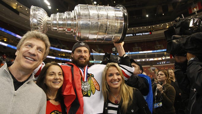 Adam Burish, shown celebrating the 2010 Stanley Cup title, has put together a charity game featuring many of his teammates from that year.