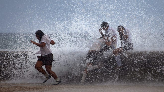 Students play in the waves crashing against the Malecon after the passing of Hurricane Sandy in Havana on Thursday.