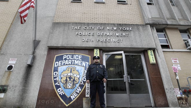 A police officer stands guard outside the 26th precinct that police officer Gilberto Valle worked.