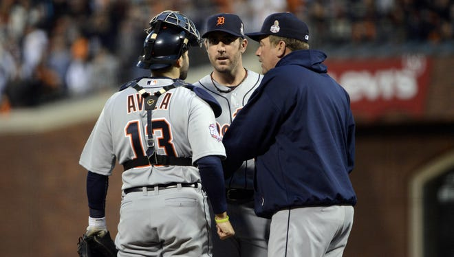 Tigers starter Justin Verlander (middle) talks with catcher Alex Avila (left) and pitching coach Jeff Jones (right) in the third inning.