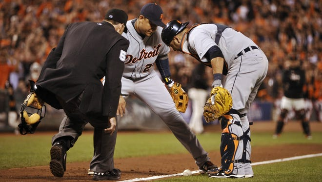 Tigers third baseman Miguel Cabrera, center, catcher Gerald Laird, right, and home plate umpire Dan Iassogna watch as a ball bunted by the Giants' Gregor Blanco hugs the fair side of the third-base line during the seventh inning.